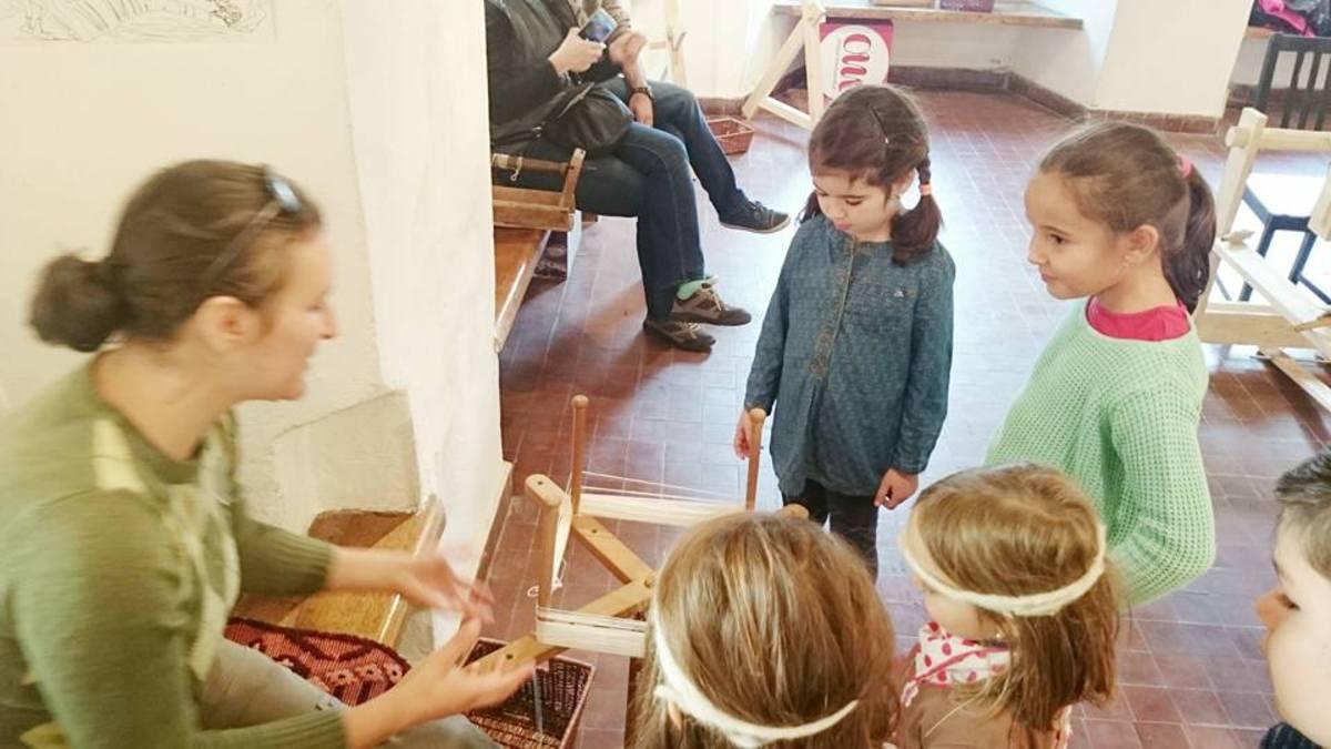 Copiii fac păpuși din pănuși de porumb și împletesc paie, în Muzeul în Aer Liber