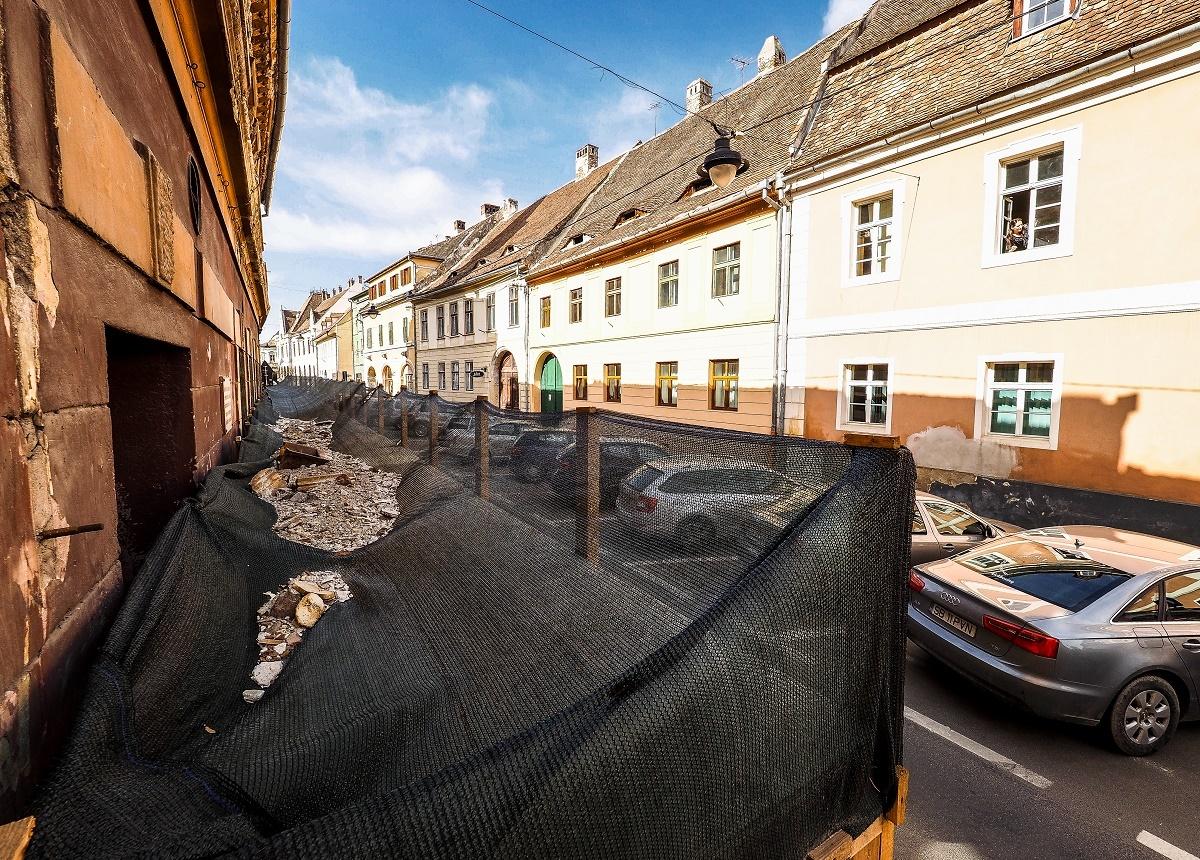TRAGEDIE EVITATĂ. Bucăți mari de tencuială s-au desprins de pe clădirea din Mitropoliei 7. Tunelul amenajat de Primăria Sibiu a oprit căderea ornamentelor în capul trecătorilor